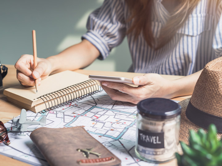 Girl sitting at desk holding phone and writing in notebook, with travel savings jar, map, and journal on desk