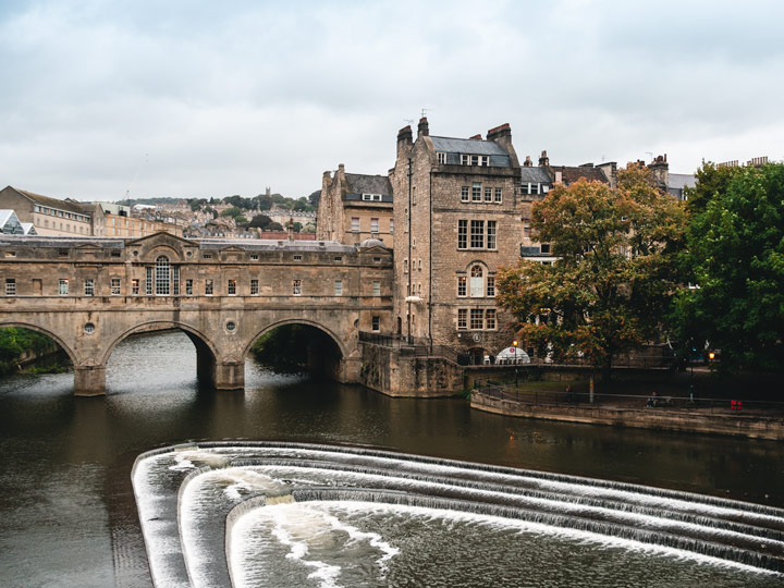 Arched stone bridge over river with small waterfalls in Bath, UK