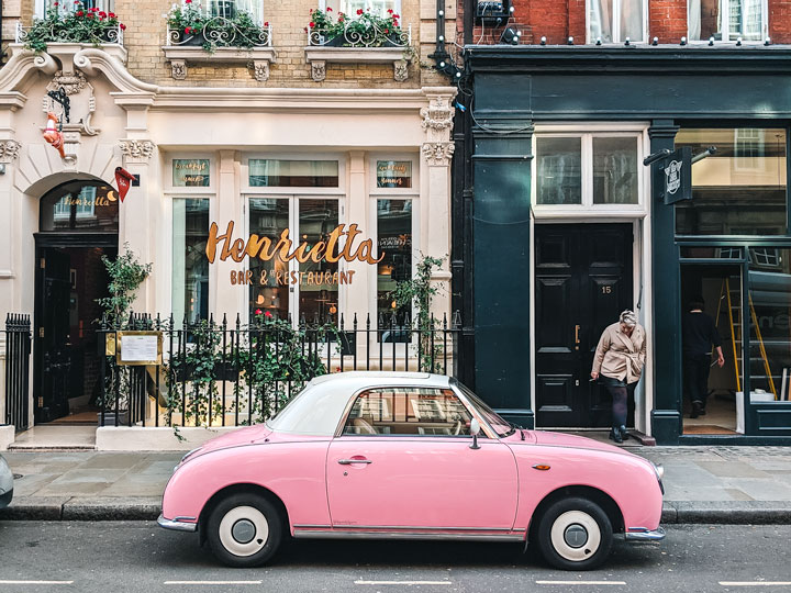 Pink classic car parked in front of white and blue buildings in London