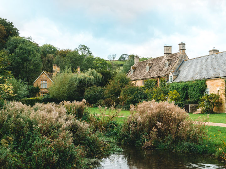 Three stone cottages in front of grassy pond in Cotswolds, visited after learning how to move to the UK