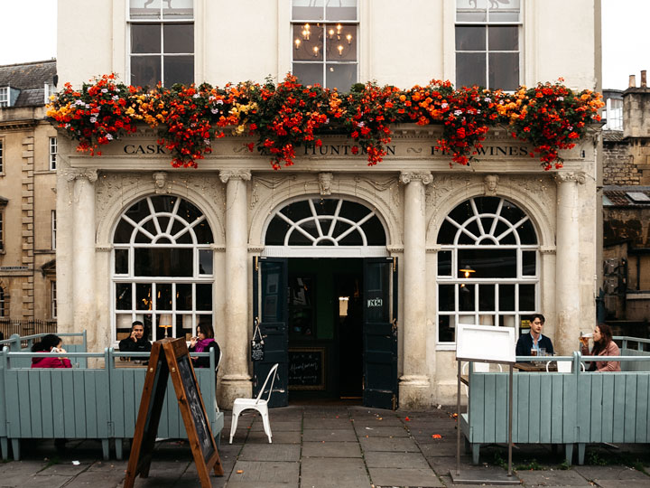 Facade of The Huntsman pub with red and yellow flowers hanging over door and blue fence in front