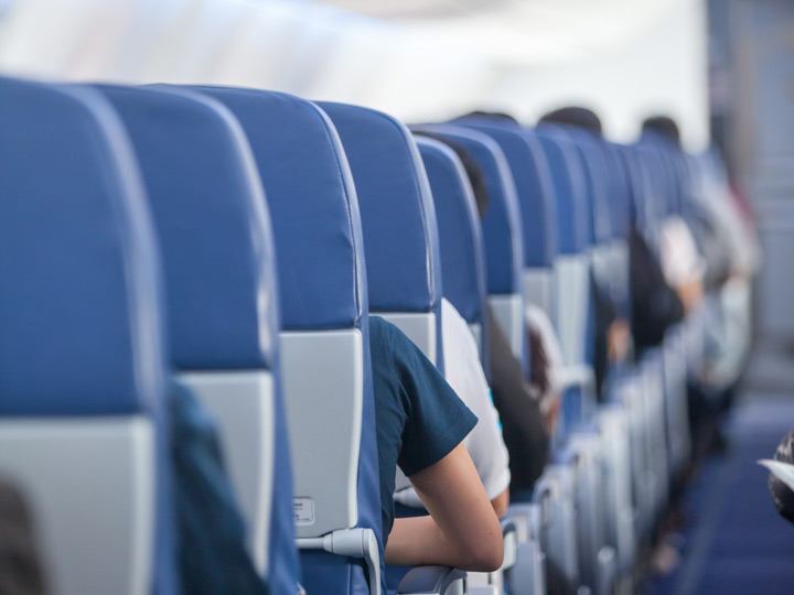 Aisle of blue airplane seats with passengers