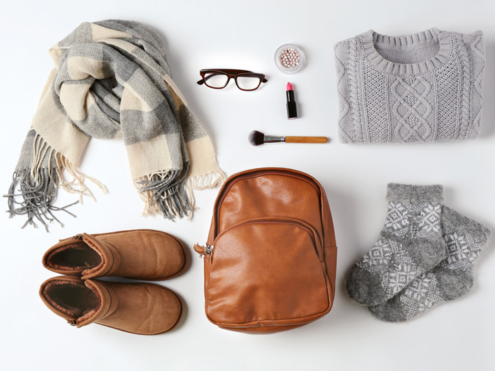Flat lay of sweater, backpack, socks, boots, scarf, and other things to wear on a long flight in economy