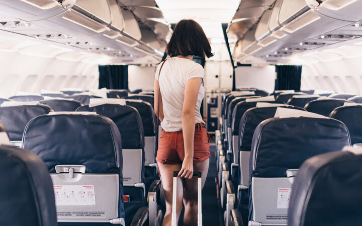 How to survive long flights in economy - girl walking down airplane aisle pulling suitcase