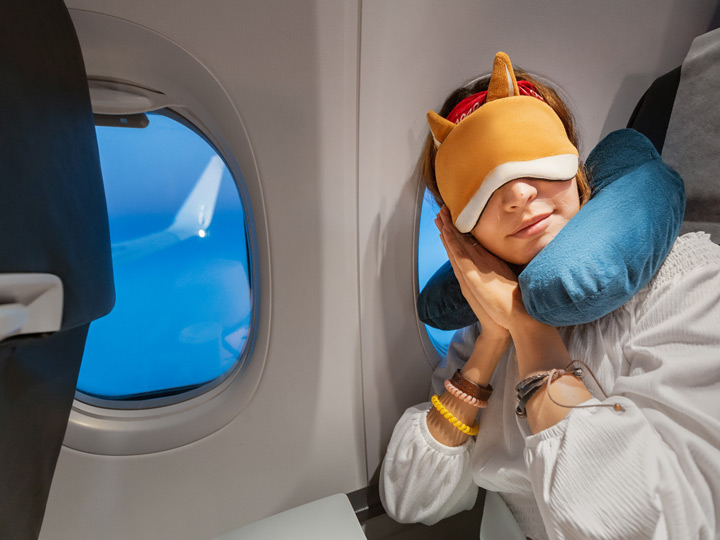 Girl on plane with fox eye mask who knows how to sleep on long flights