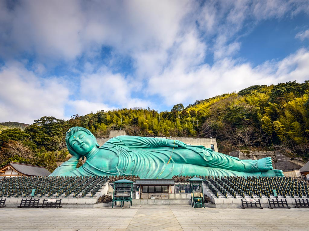 Large blue reclining Buddha statue with forested mountain in background