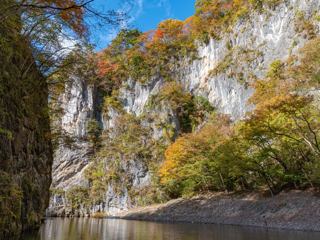 Autumn view of trees and white cliff sides of Geibikei Gorge