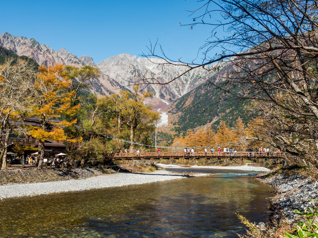 Wooden bridge crossing river with mountain backdrop in Kamikochi park