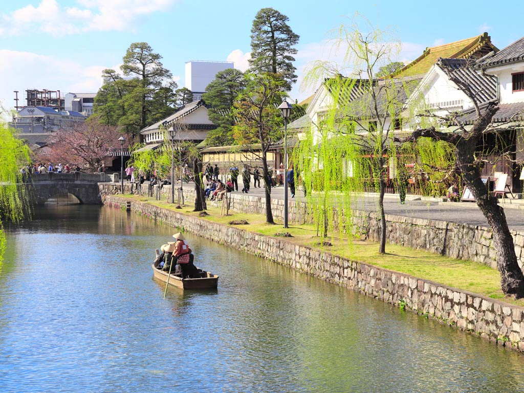Traditional boat traveling down canal lined with trees in Kurashiki Japan off the beaten path