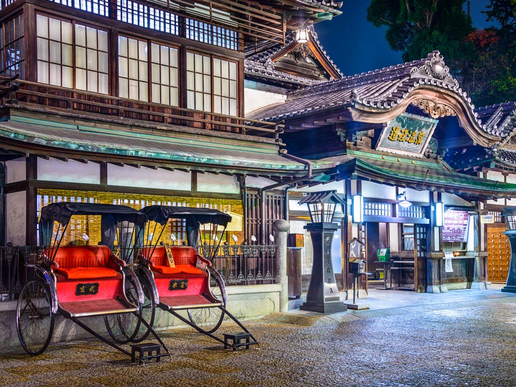 Nighttime exterior of Dogo Onsen in Matsuyama with two red rickshaws out front