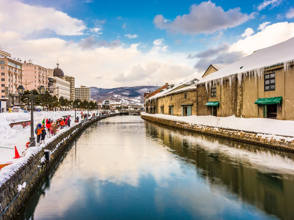 Wintery scene of Otaru canal and warehouses with partly cloudy sky