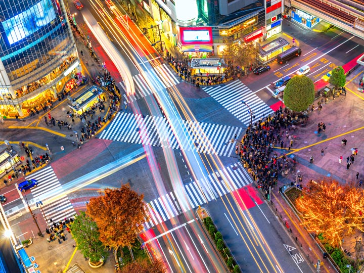 Tokyo Shibuya Crossing with light trails and people waiting to cross the street