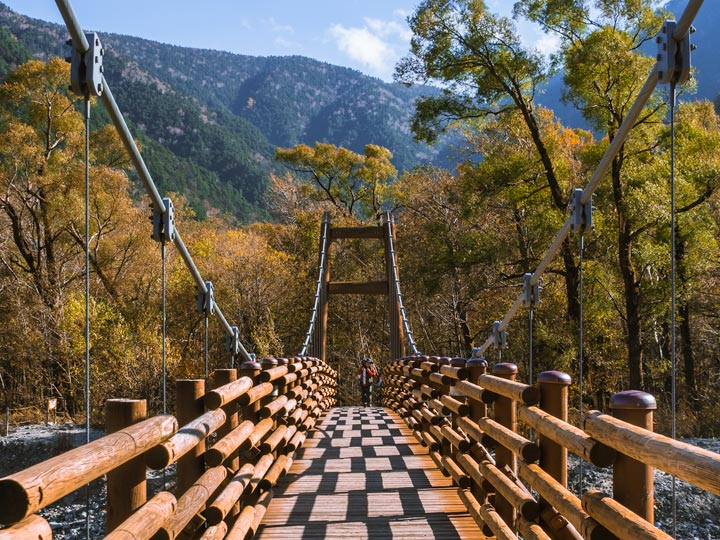Man walking across wooden Myojin Bridge while hiking Kamikochi park in autumn