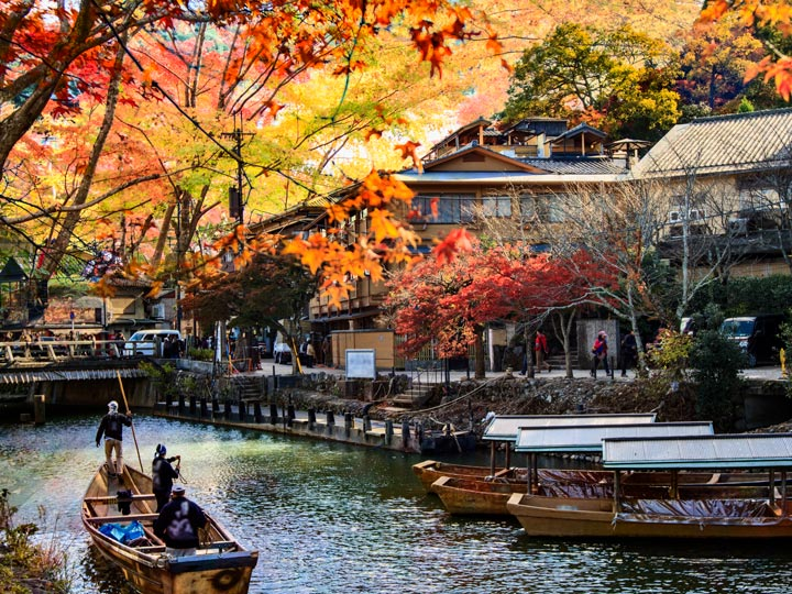 Arashiyama river with traditional boats and autumn leaves overhead