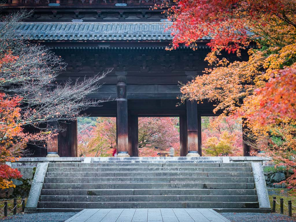 Nanzenji temple gate with autumn leaves framing sides, a must see during a Kyoto 2 day itinerary