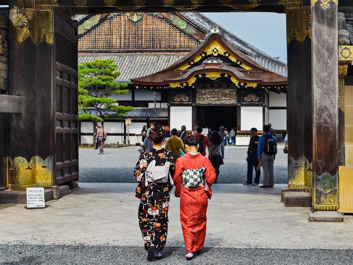 Two women in kimonos walking through gate of Nijo Castle
