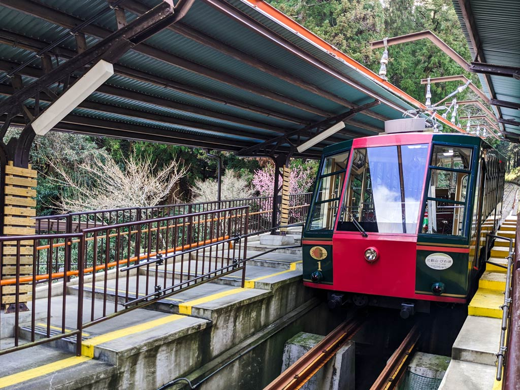 Red and green cable car pulling into open air station at Cable Sakamoto
