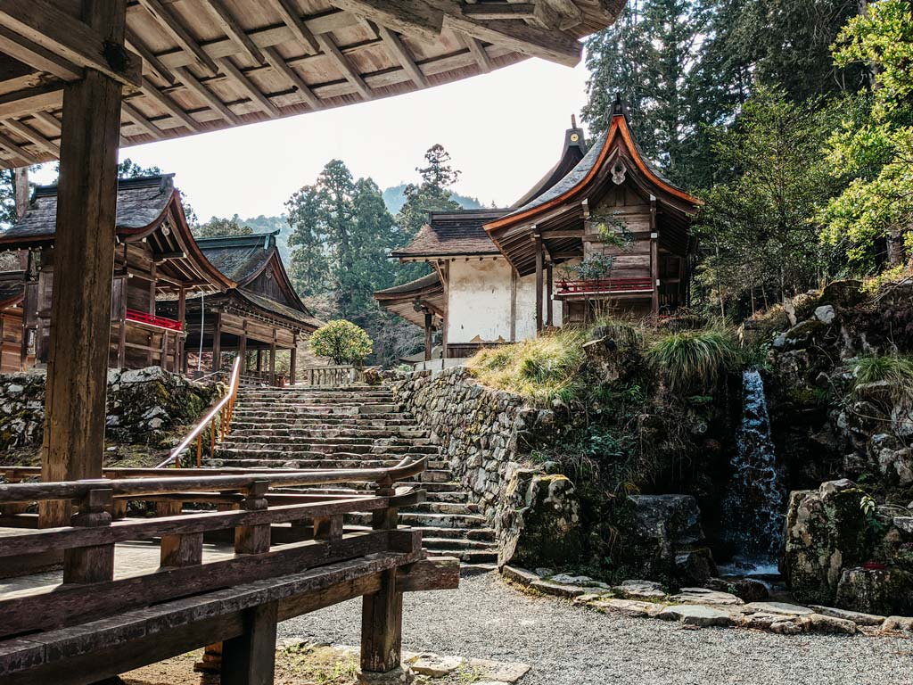 View of old wooden shrine buildings and small waterfall insdie Hiyoshi Taisha shrine complex