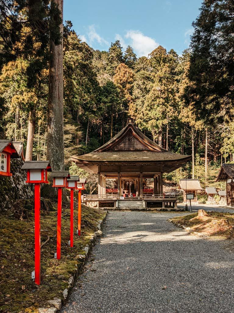 Pebble path with orange lanterns leading to old wooden shrine