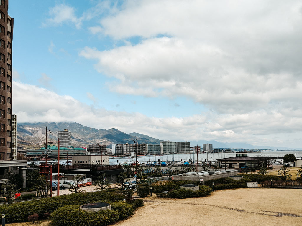 View of Otsu Port with ships and brown grass in foreground, and lake and mountains in the distance