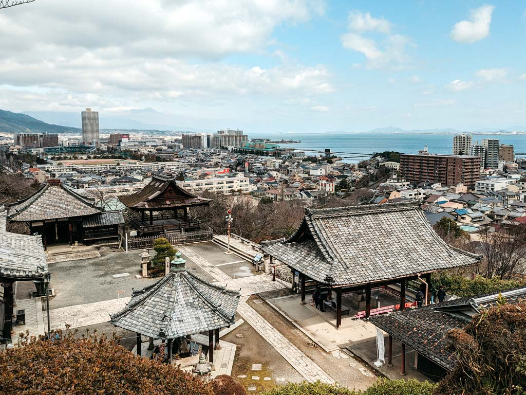 Mii-dera shrine viewed from a hill overlooking the roofs, along with cityscape and Lake Biwa