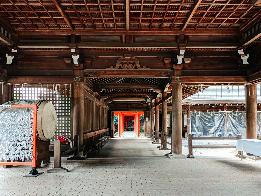 Interior of Omi-Jingu main hall with old drum, carved wooden ceiling, and view down torii gate path
