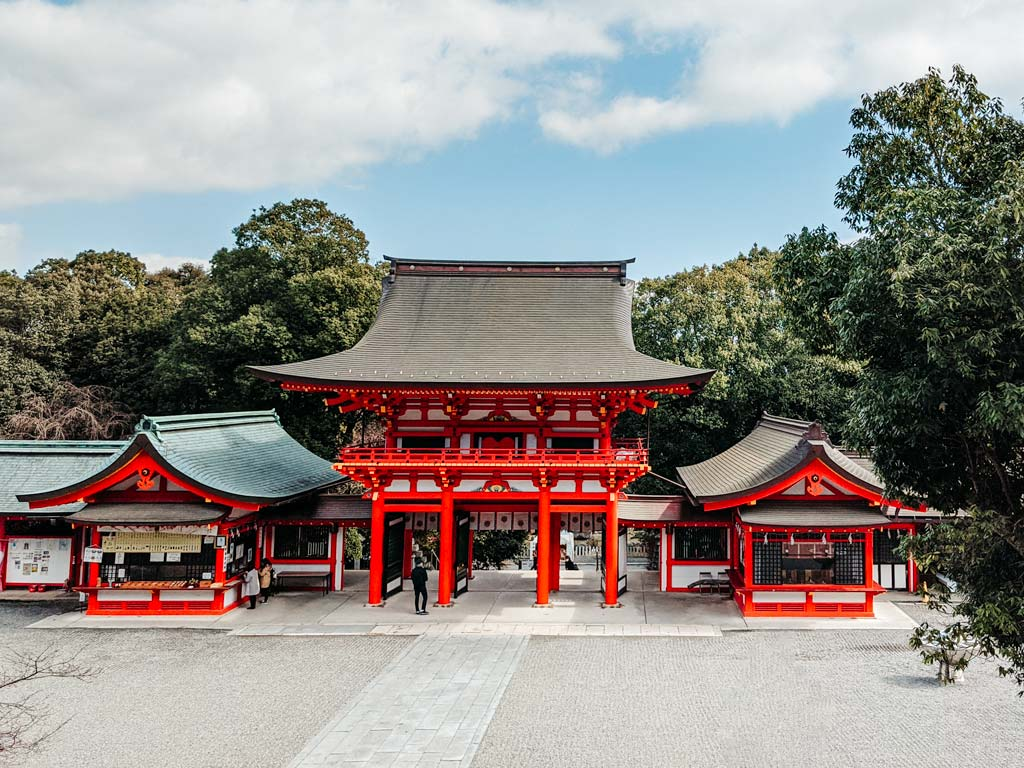 Vermillion and white gate of Omi-Jingu shrine with trees behind