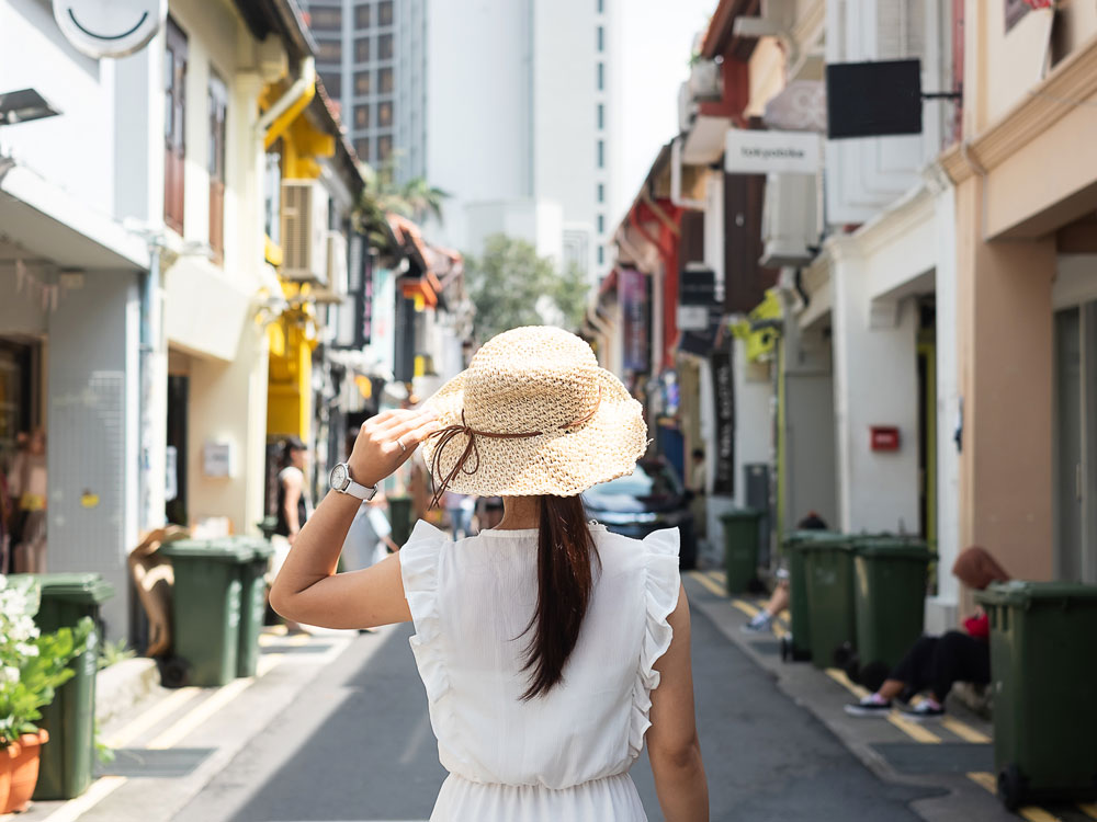 Girl in white dress holding straw hat walking down alley, living the life of an expat
