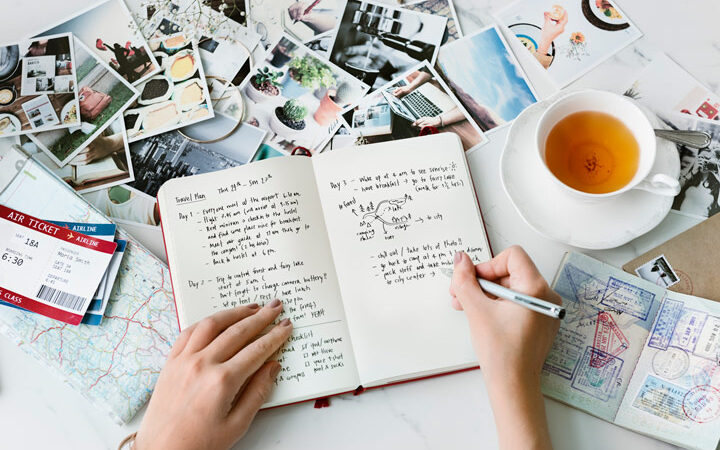 Person writing living abroad quotes in journal on white table with tea cup, photos, and plane tickets