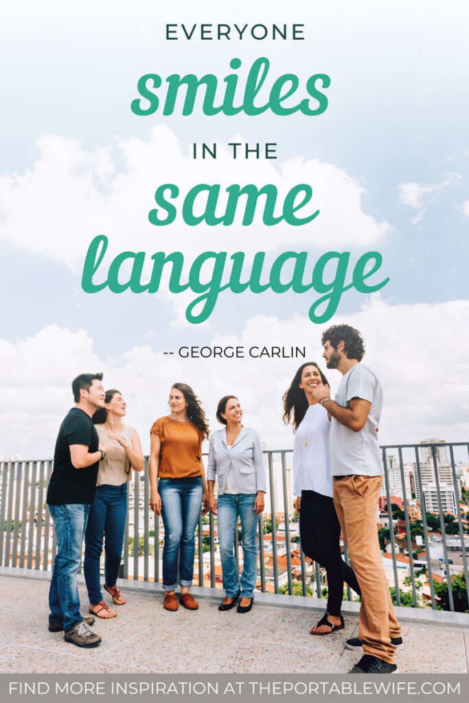 """Six people talking on rooftop deck with text overlay - """"Everyone smiles in the same language."""""""