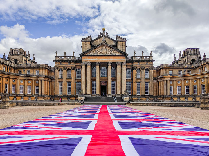 British flag walkway leading to Blenheim Palace entry with dozens of windows and columns