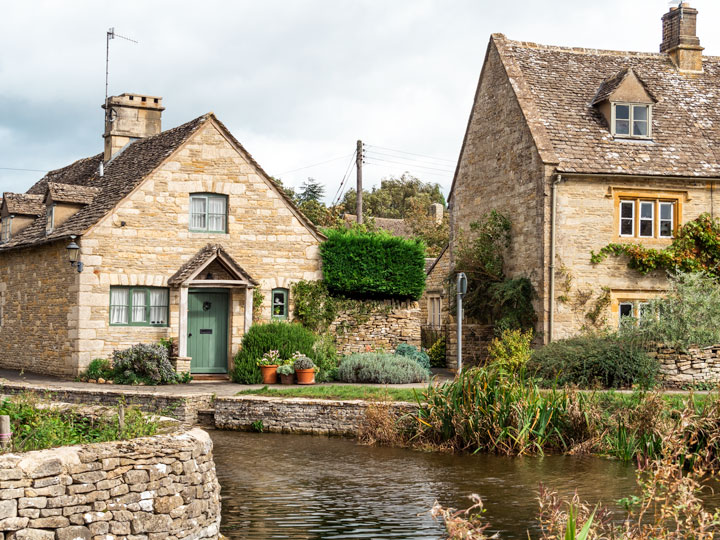 Living in England pros and cons include visits to this beautiful Cotswolds stone cottage on a canal