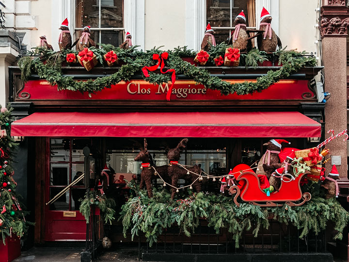 Christmas display with red sleigh and penguins at London restaurant
