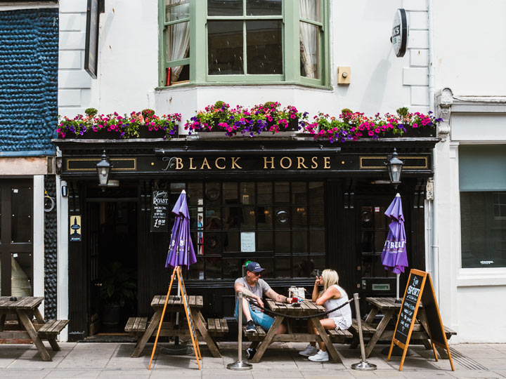 Two people discussing living in England pros and cons at table in front of Black Horse pub