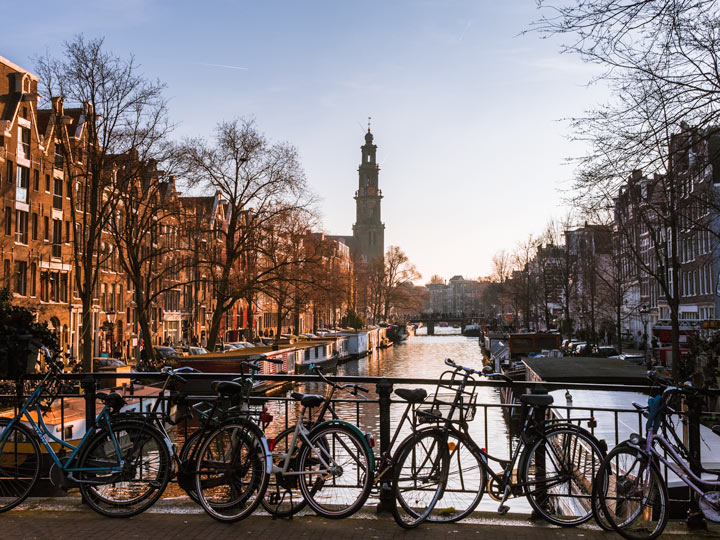 Sunset view of Amsterdam canal bridge with bikes against railing