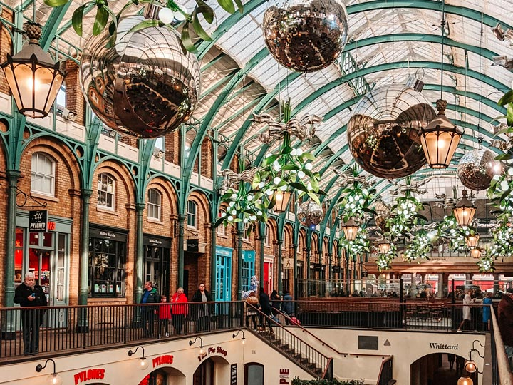 London Covent Garden Christmas market with large silver ornaments hanging from ceiling