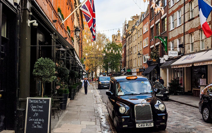 Busy London streets with flags and black cabs are among the living in London pros and cons