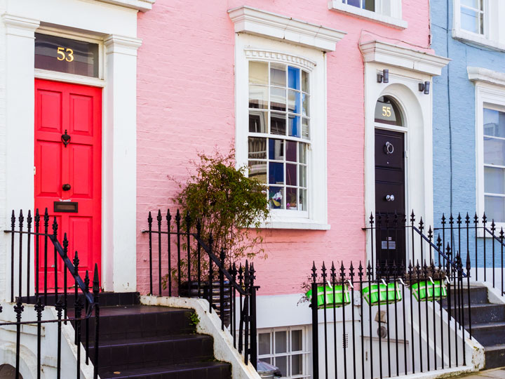 London row homes with pink and blue facades and pink and black doors