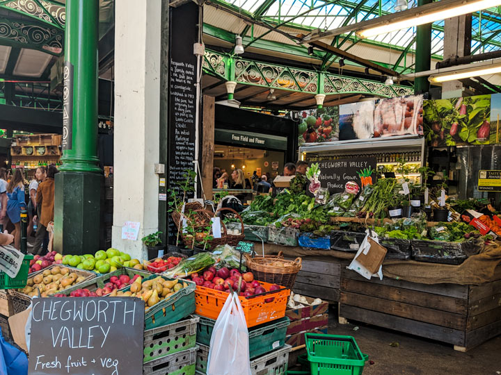 London grocery stores inside Borough Market with bins of produce and wooden crates of vegetables