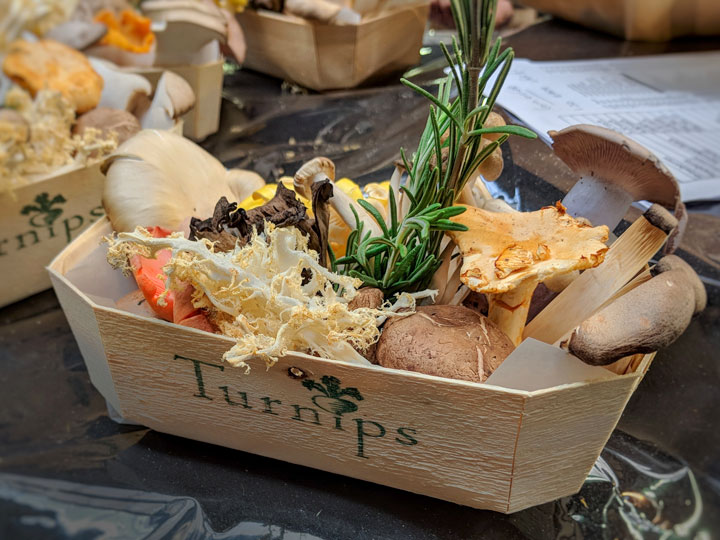 Wooden carton of wild mushrooms and thyme sprig