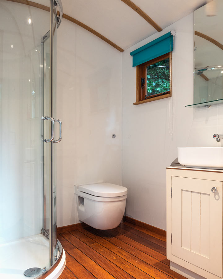 Private washroom with toilet, sink, and glass shower at Kenton Hall Estate