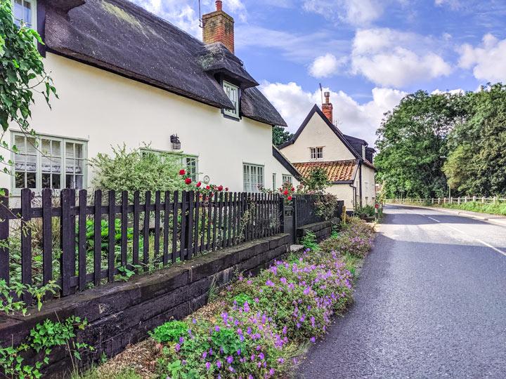 Thatched roof cottages with flower garden on street in Debenham Suffolk