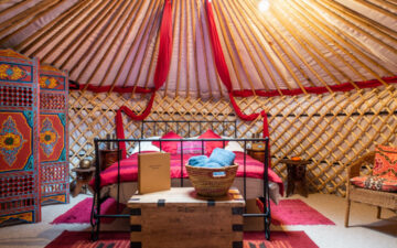 Luxury Glamping in Suffolk - Kenton Hall Estate yurt interior with red bed, chest, and screen