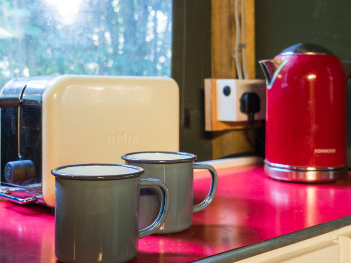 Toaster, mugs, and tea kettle on glamping kitchen counter
