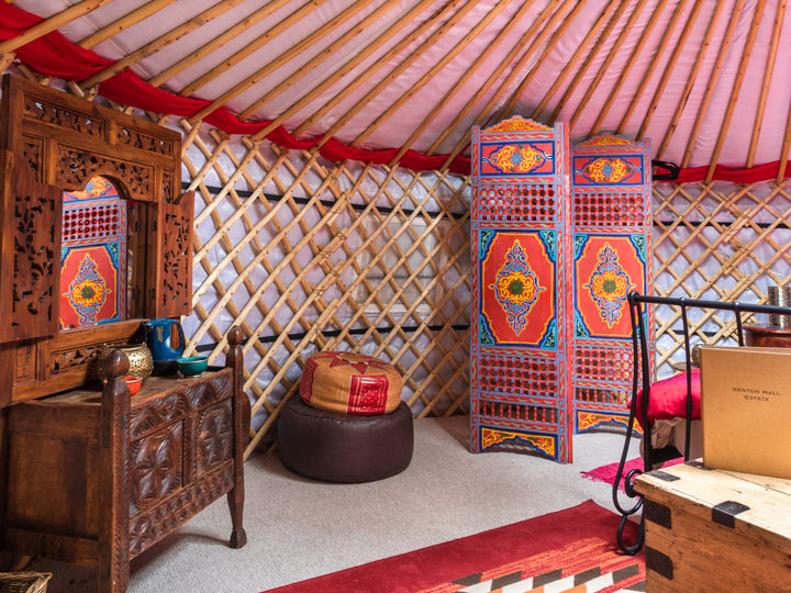 Glamping yurt interior with wooden dressing table, poufs, and screen