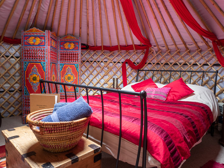 Yurt interior with red bed, wooden chest, towel basket, and screen
