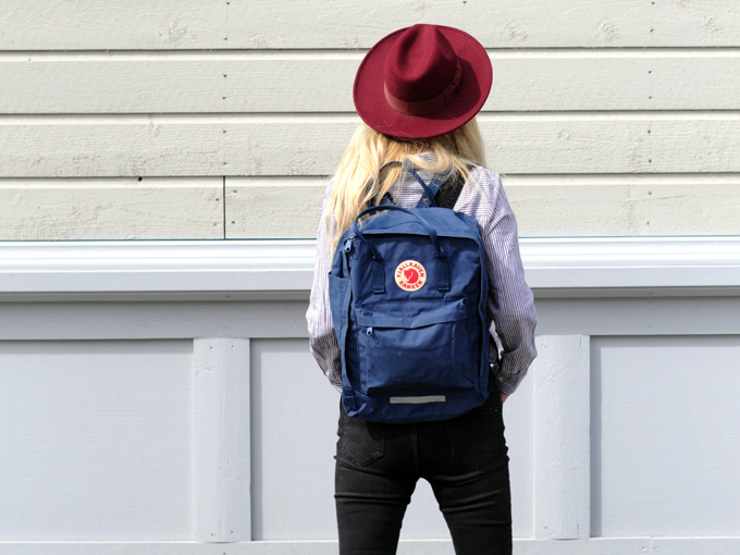 Woman wearing mix and match travel wardrobe of black jeans, red hat, and blue backpack