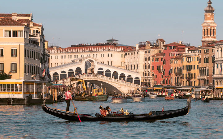 Sunset on Venice Grand Canal with gondola in foreground, one of the most Instagrammable places in Europe