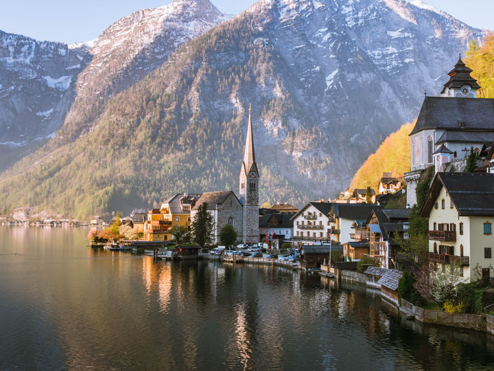 Panoramic view of Hallstatt village with lake in foreground and mountains in distance