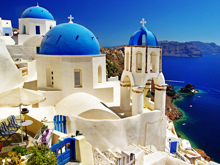 Whitewashed house with blue dome roofs overlooking ocean in Oia